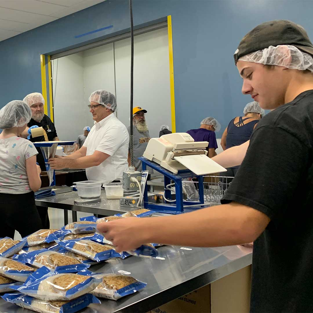 First Impressions Ironworks Employees Preparing Meals at Feed My Starving Children
