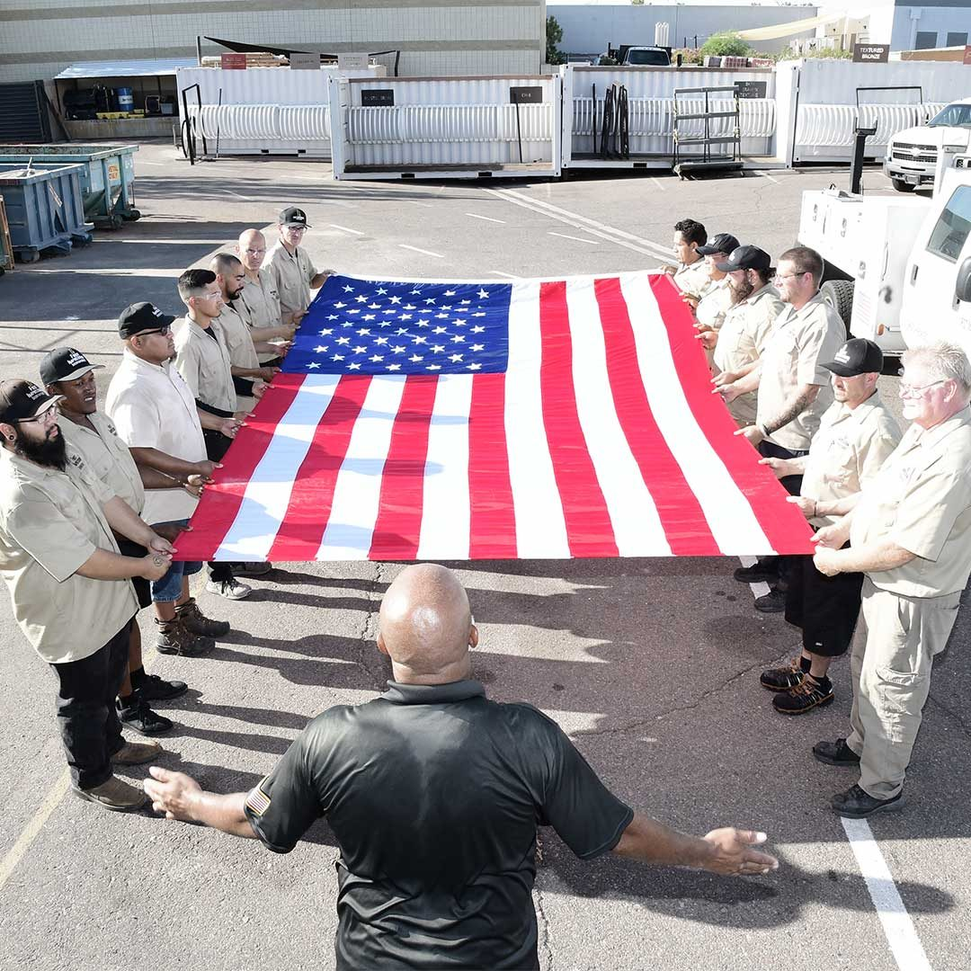 First Impression Ironworks Employees Holding A Large Flag