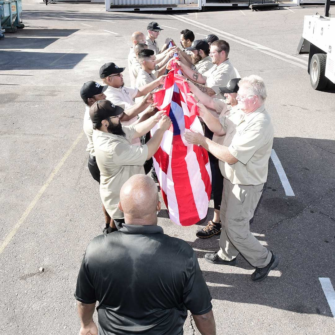 First Impression Ironworks Employees Folding A Large Flag