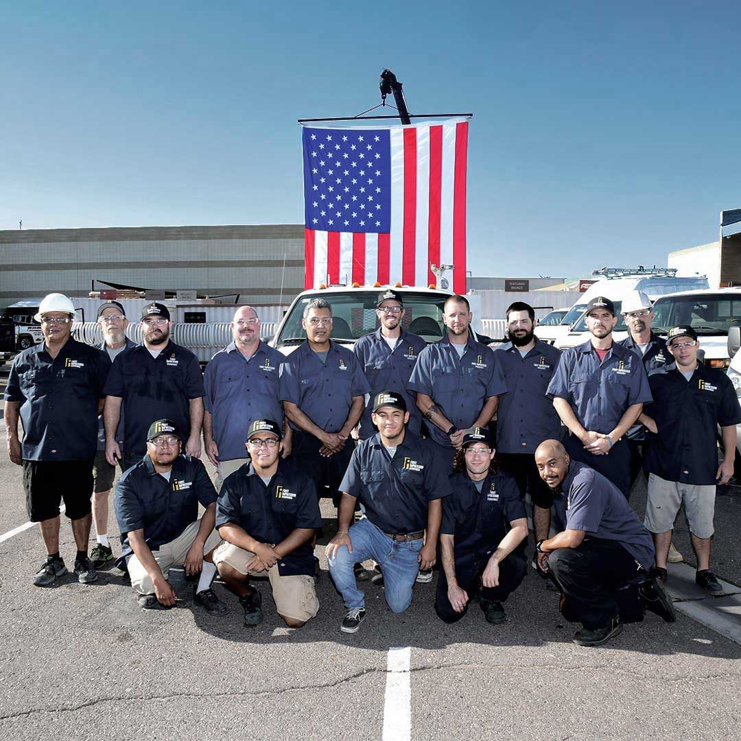 Group of First Impression Ironworks Employees With Flag Behind Them