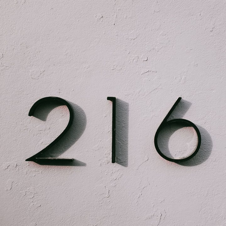 Black home address numbers (216) on an outdoor white wall