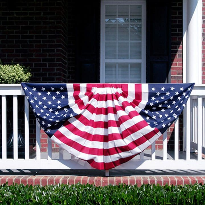 Patriotic bunting hanging from white front porch railing