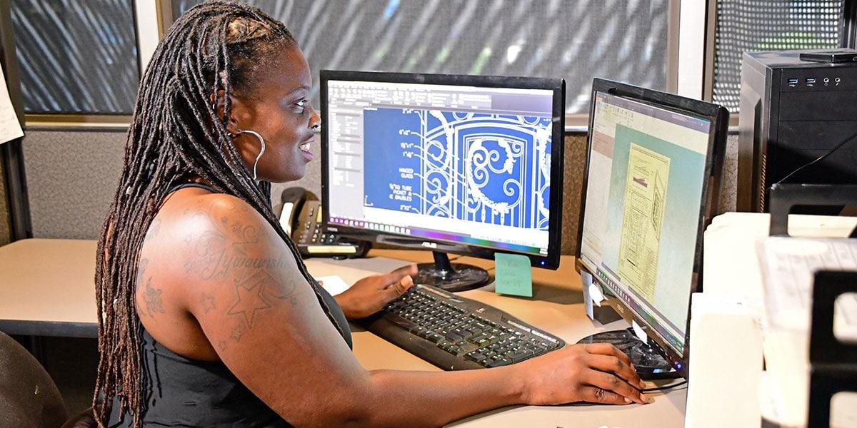 First Impression Ironworks CAD Designer working on her computer at her desk