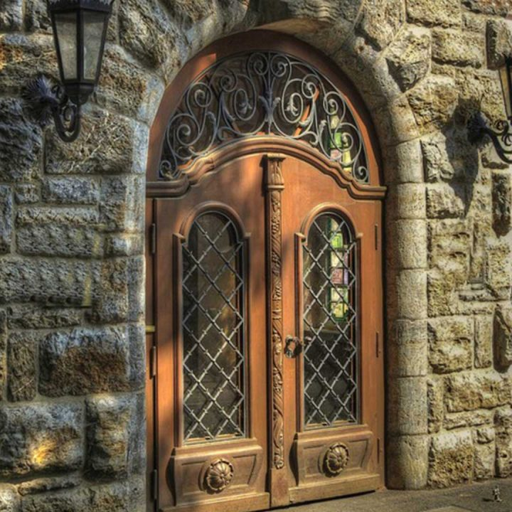 large arched wooden and glass door surrounded by an old stone building