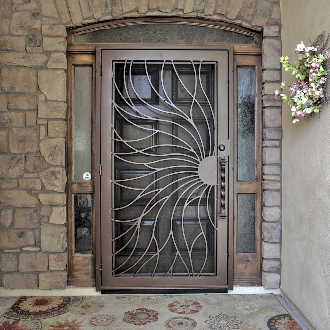 dark bronze colored iron security door with a sun shaped design