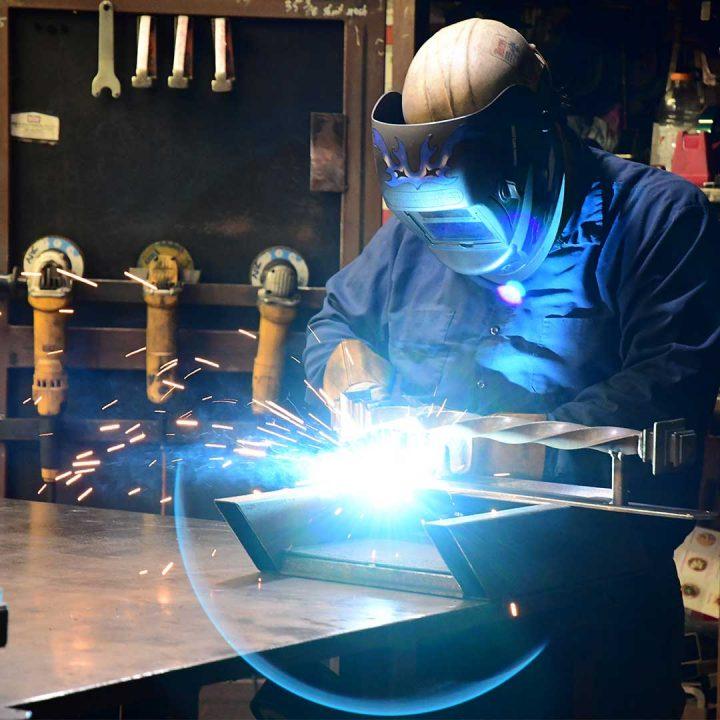 First Impression Ironworks employee welding a steel door part