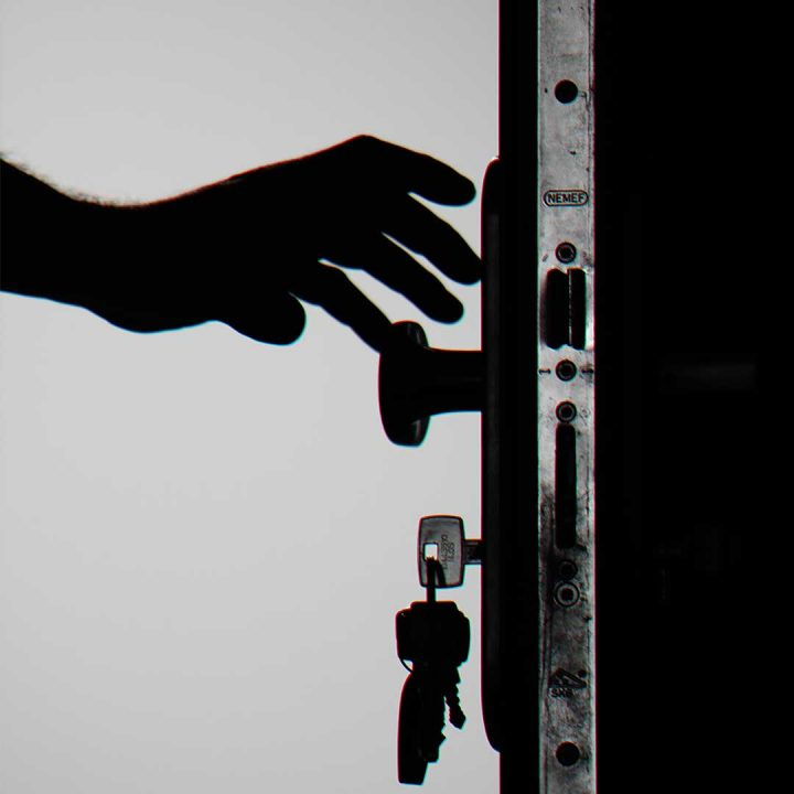 silhouette of a hand reaching to open a front door