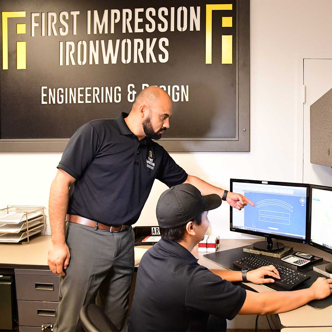 First Impression Ironworks Member pointing at a computer monitor