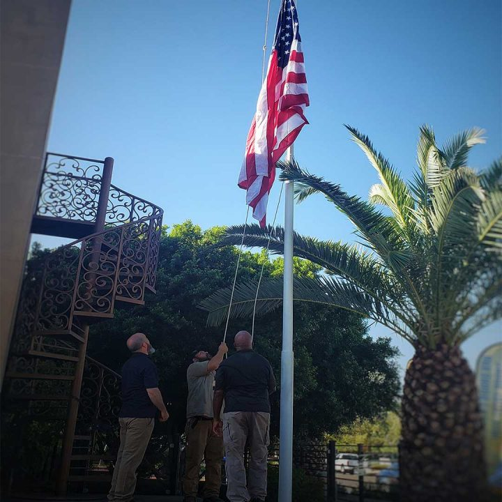 First Impression Ironworks Employees raising flag at their Gilbert showroom