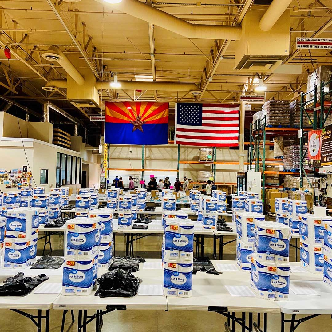 Warehouse filled with tables full of supplies to be packed for food boxes