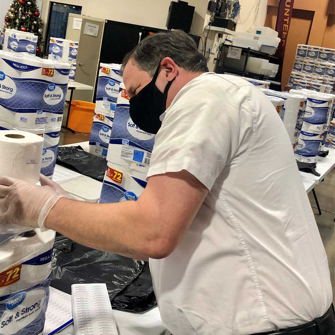 Volunteer stacking rolls of toilet paper to be added to donation boxes