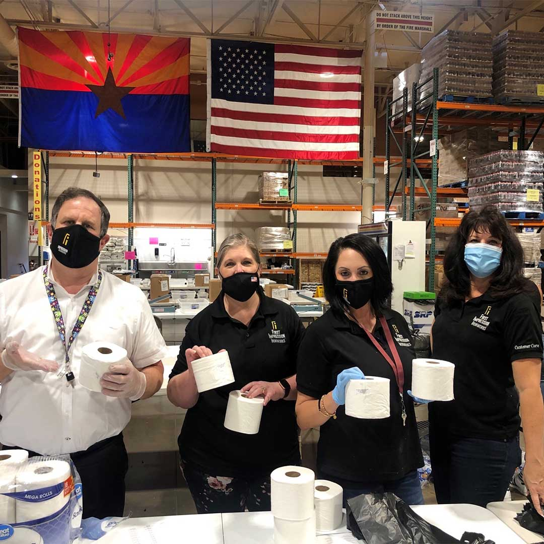 First Impression Ironworks team members holding multiple rolls of toilet paper that are being packed into donation boxes