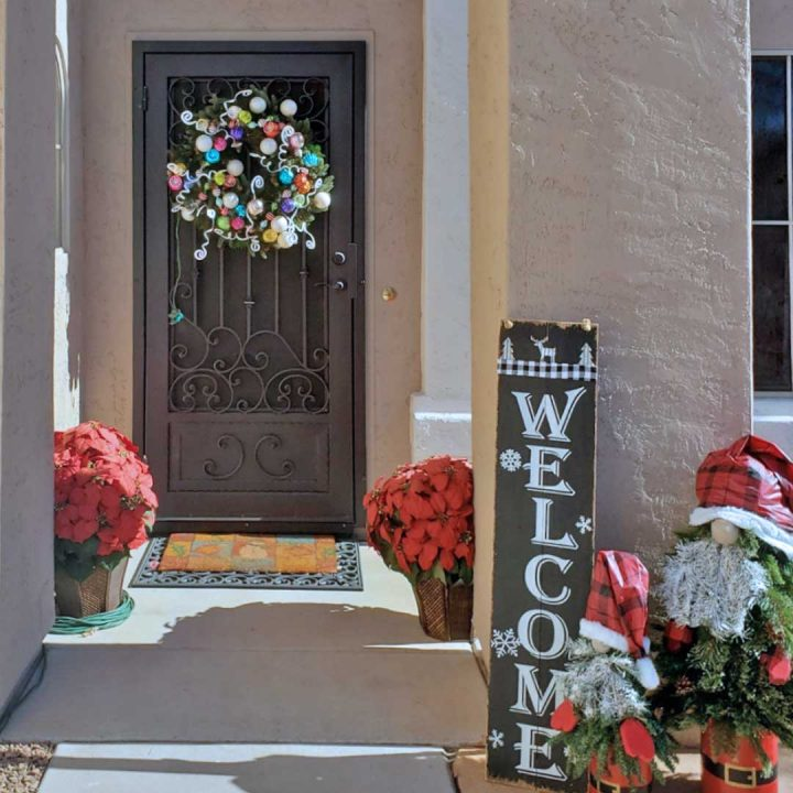 First Impression Ironworks iron security door decorated with a holiday wreath.  ENtryway is decorated with various holiday decorations