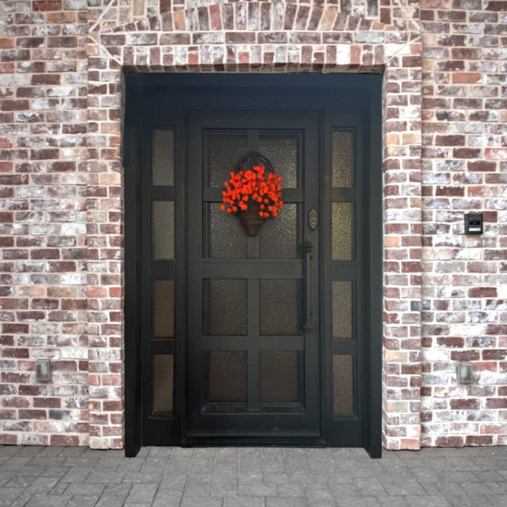 Brick home with an iron and glass First Impression Ironworks front door, with a holiday basket hanging from the door.