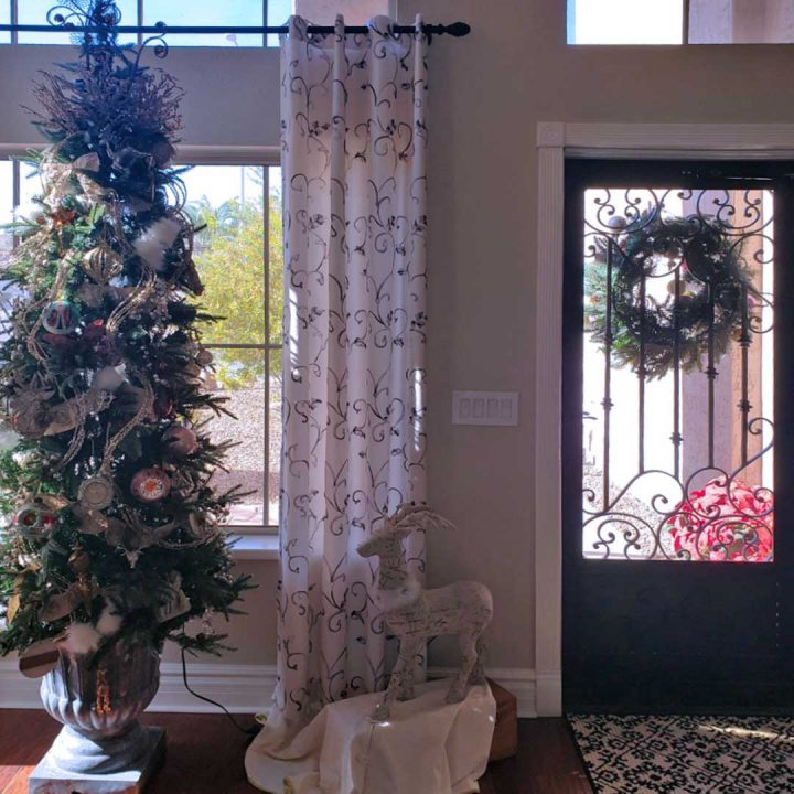 Interior view of a First Impression Ironworks security door.  Inside of the home is decorated for Christmas, including a Christmas tree.
