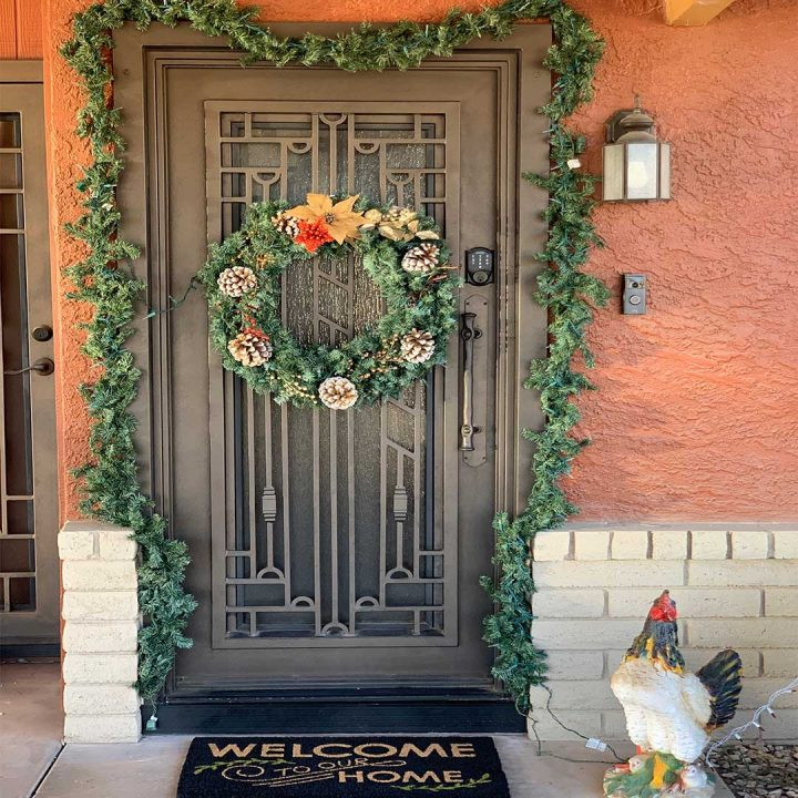 First Impression Ironworks Iron Entry Door with a large wreath hanging from it.  Door is surrounded by holiday garland