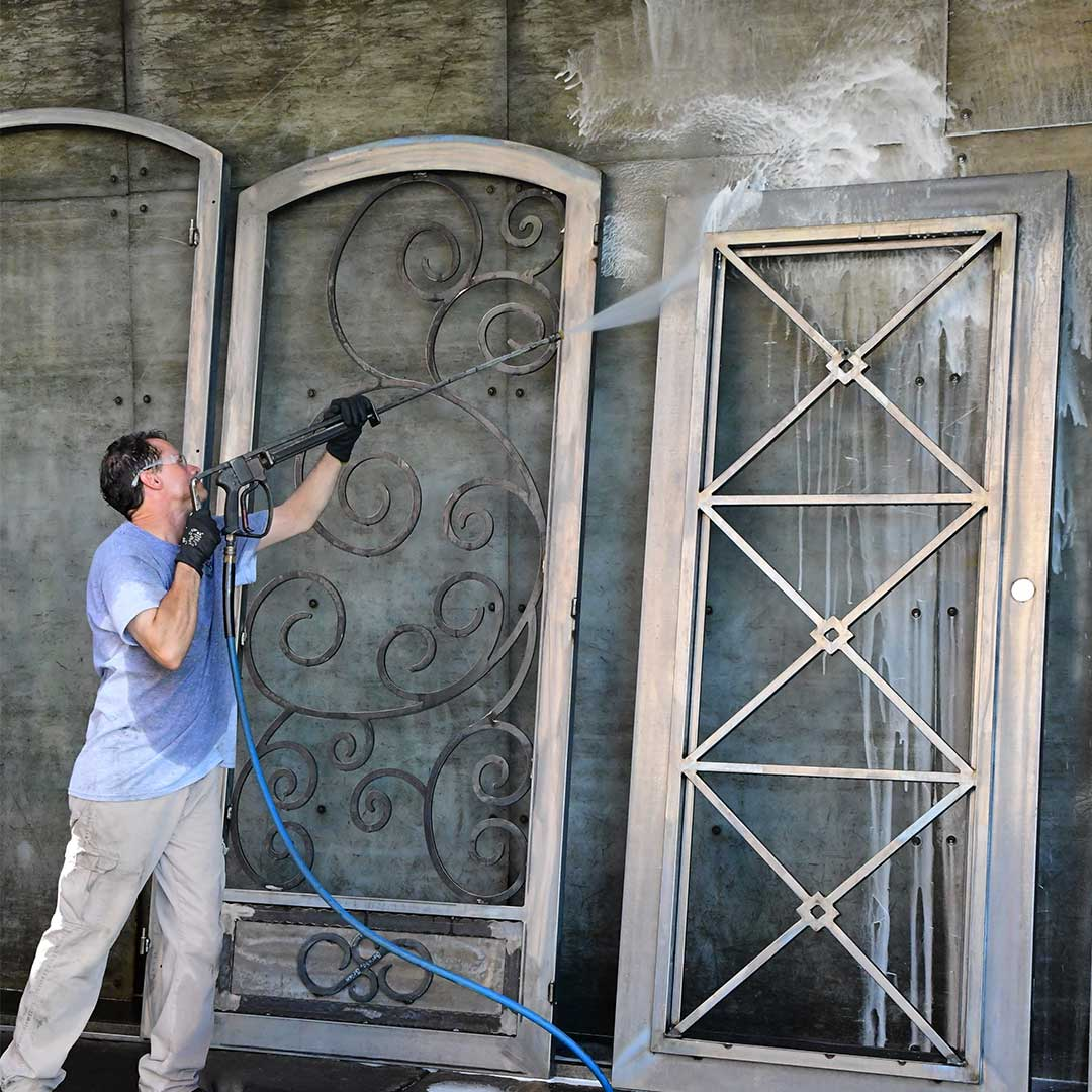 First Impression Ironworks employee spraying iron doors with phosphate wash
