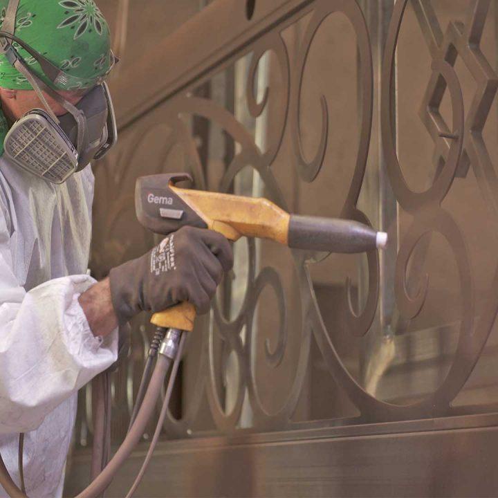 First Impression Ironworks employee powder coating an iron door