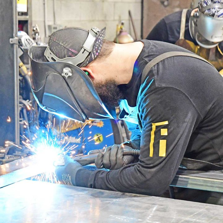 First Impression Ironworks employee welding an iron door