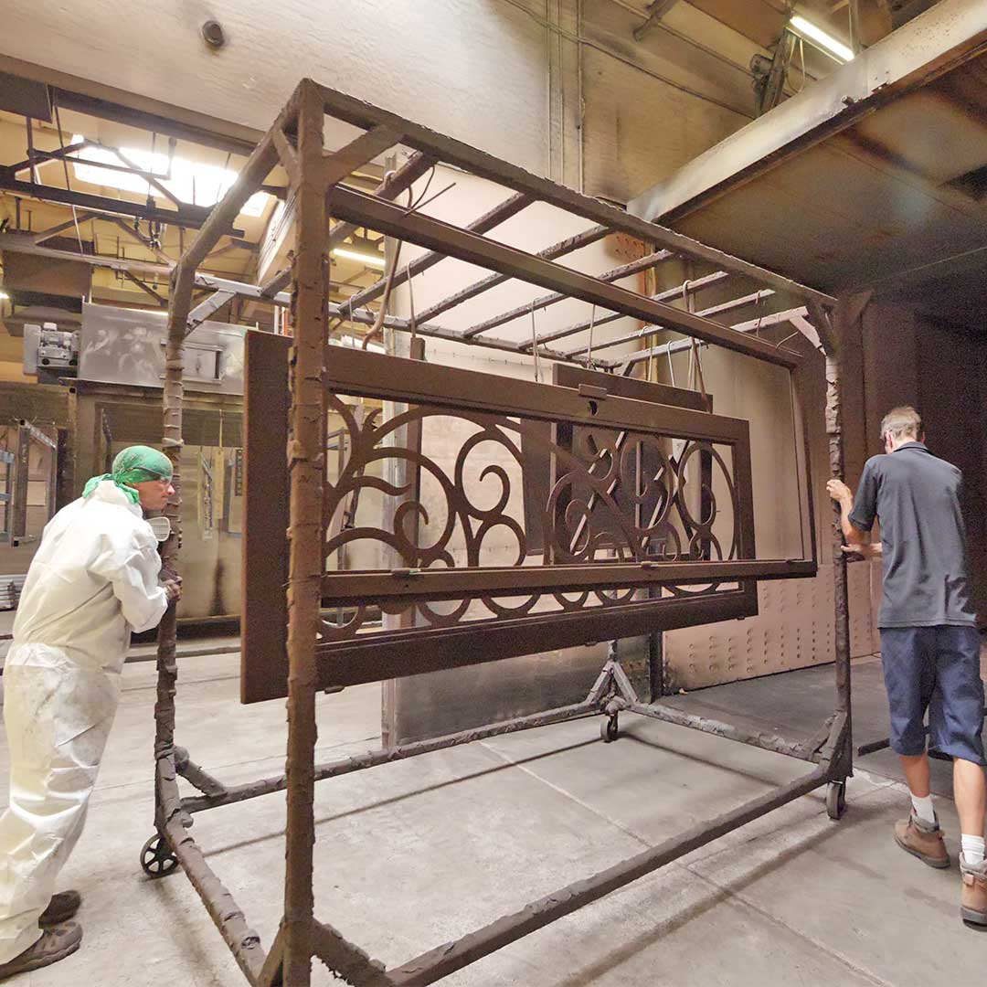 Two First Impression Ironworks employees rolling iron doors into the oven to bake the powder coat