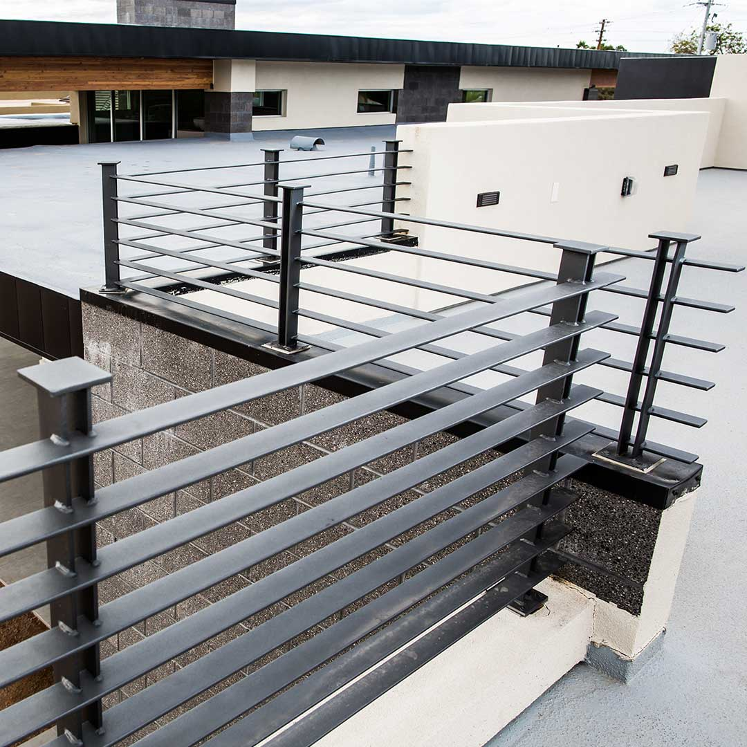Close up picture of a rooftop balcony railing made of iron