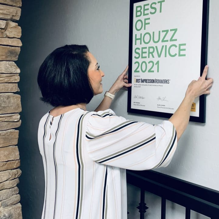 Shannon hanging the Best of Houzz service award on the wall