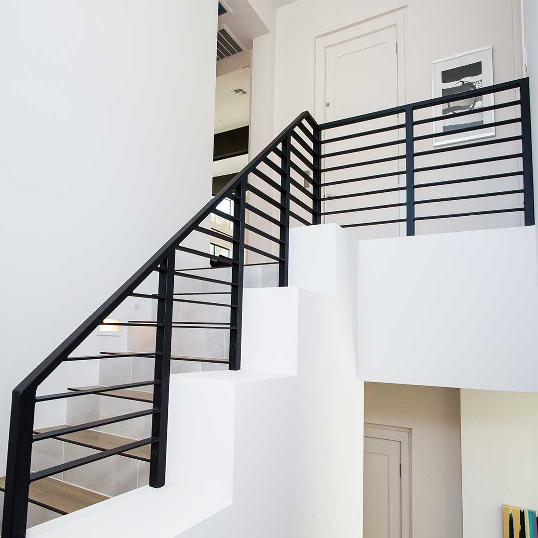 staircase with a modern black iron railing