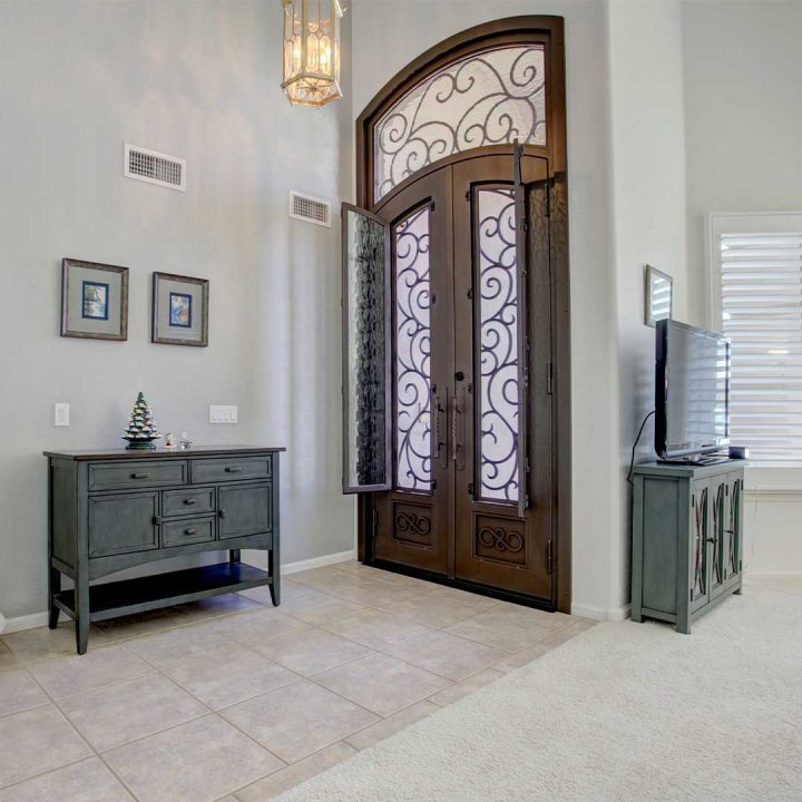 Inside the entryway of a home with large iron and glass French doors.