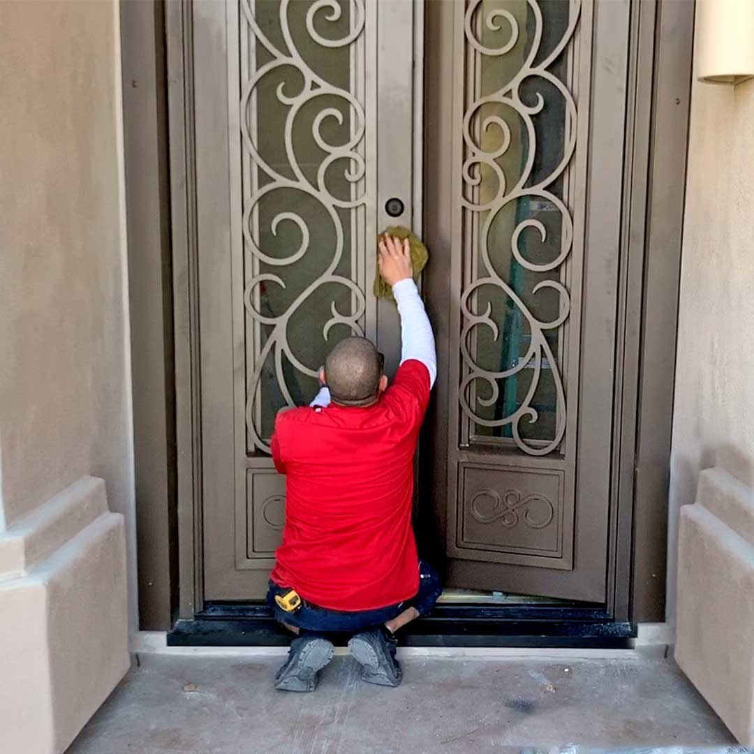 Man cleaning a First Impression Ironworks Iron Entry Door