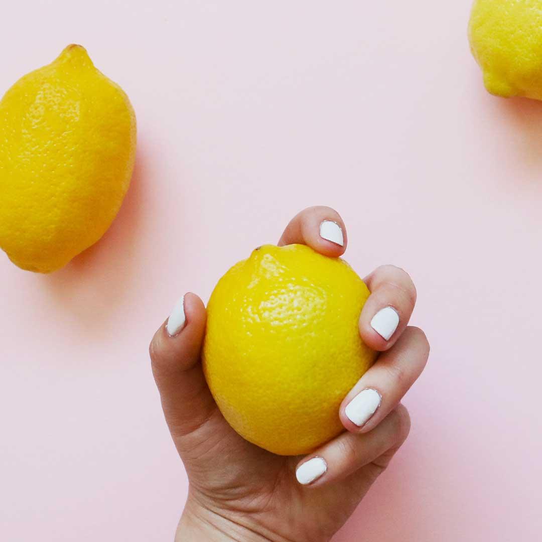 a hand holding a lemon