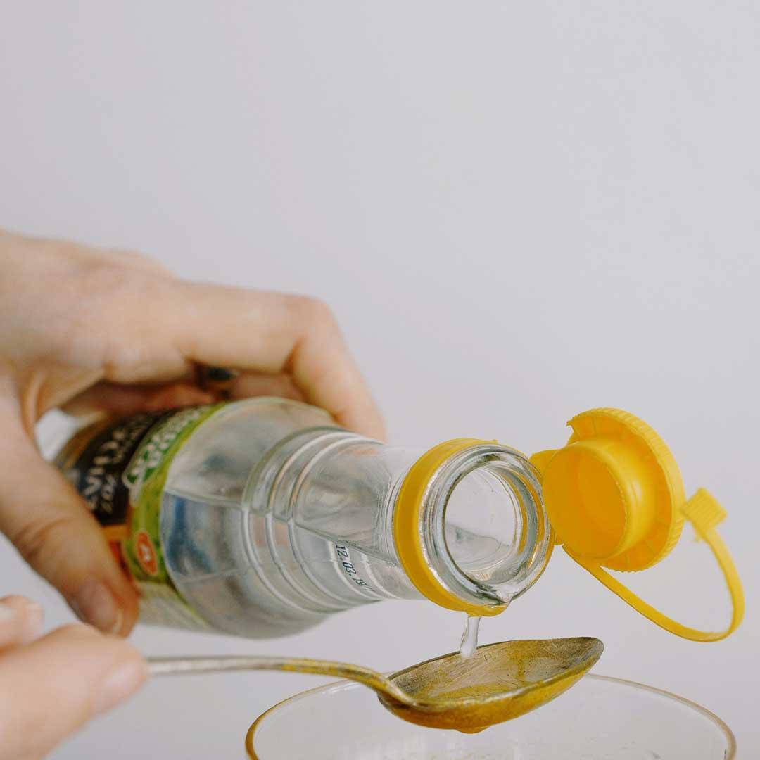 pouring white vinegar into a spoon